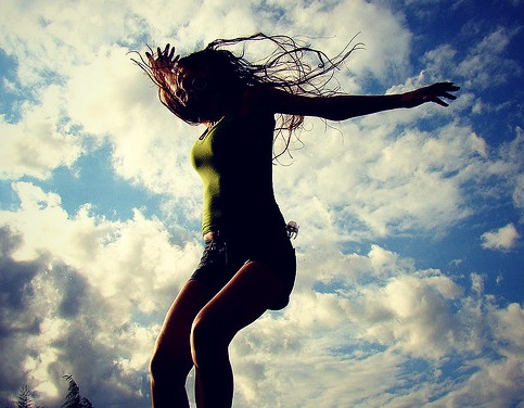 Girl jumping in front of the sky